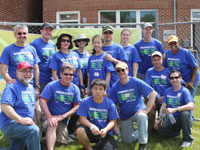 OCC volunteers take a break from cleaning up to gather outside the new Bexhill condominiums, which were developed by Manna, a NeighborWorks affiliate.